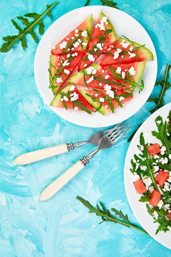 Ensalada fresca de la sandía del verano con el queso feta y el arugula en fondo azul de la tabla Comida del vegano Dieta, vegetar foto de archivo libre de regalías
