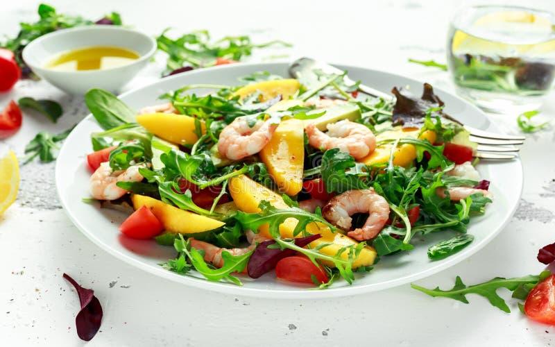 Ensalada fresca del aguacate, de los camarones, del mango con la mezcla del verde de la lechuga, tomates de cereza, hierbas y ace foto de archivo libre de regalías