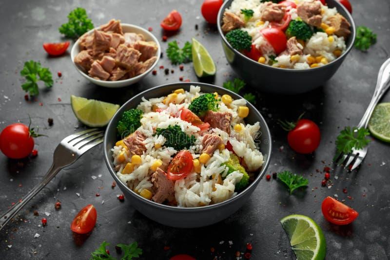 Ensalada fresca del arroz del atún con maíz dulce, los tomates de cereza, el bróculi, el perejil y la cal en cuenco negro fotos de archivo