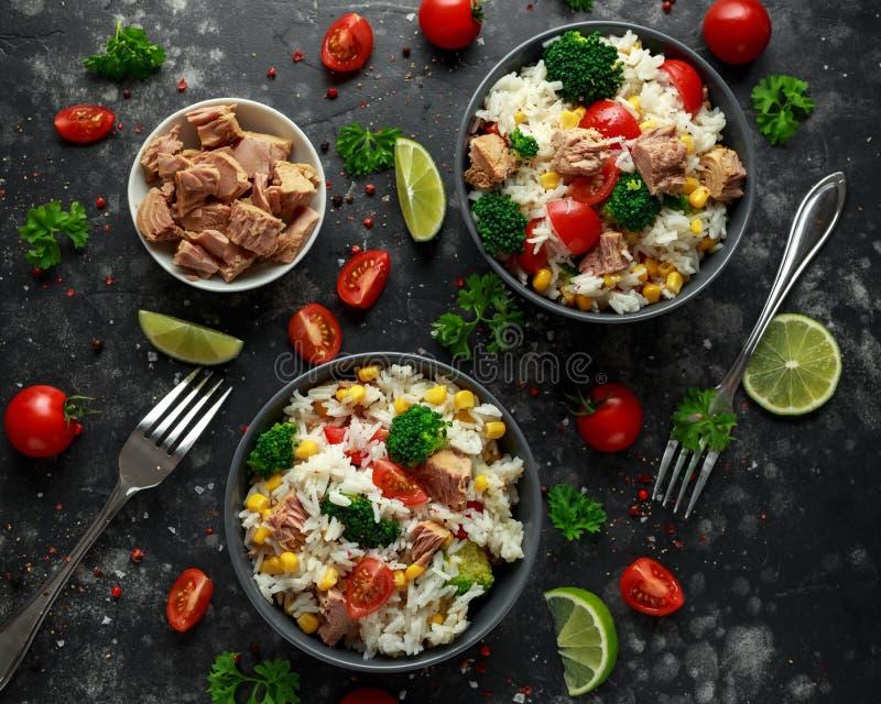 Ensalada fresca del arroz del atún con maíz dulce, los tomates de cereza, el bróculi, el perejil y la cal en cuenco negro fotografía de archivo