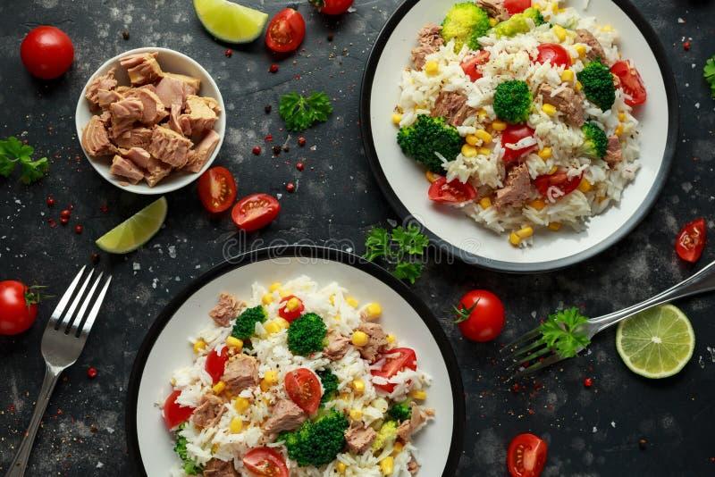 Ensalada fresca del arroz del atún con maíz dulce, los tomates de cereza, el bróculi, el perejil y la cal en cuenco negro imagenes de archivo