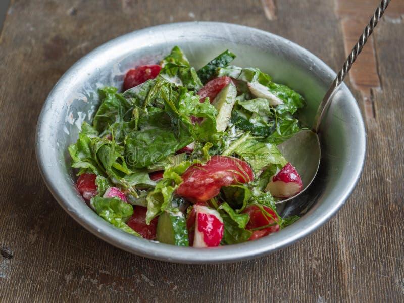 Ensalada fresca del verano de tomates, de pepinos y de hierbas aromáticas en un cuenco profundo con una cuchara, con crema agria  foto de archivo libre de regalías