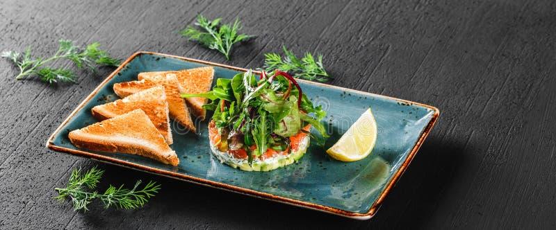 Ensalada fresca sana con el aguacate, los salmones, los verdes, arugula, espinaca y queso con la tostada en placa sobre fondo osc imagenes de archivo