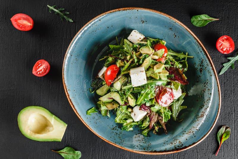 Ensalada fresca sana con el aguacate, verdes, arugula, espinaca, los tomates de cereza y el queso en placa sobre la tabla oscura  imagen de archivo libre de regalías