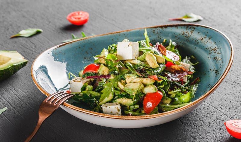 Ensalada fresca sana con el aguacate, verdes, arugula, espinaca, los tomates de cereza y el queso en placa sobre la tabla oscura  foto de archivo