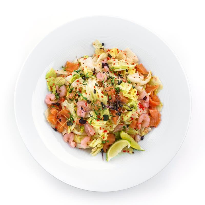 Ensalada fresca sana con la lechuga, verdes, caviar rojo, camarón, salmón del prendedero en placa en fondo blanco aislado Comida  foto de archivo libre de regalías