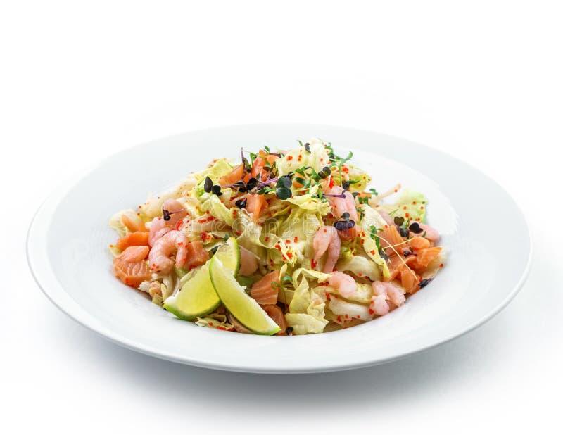 Ensalada fresca sana con la lechuga, verdes, caviar rojo, camarón, salmón del prendedero en placa en fondo blanco aislado Comida  fotos de archivo libres de regalías