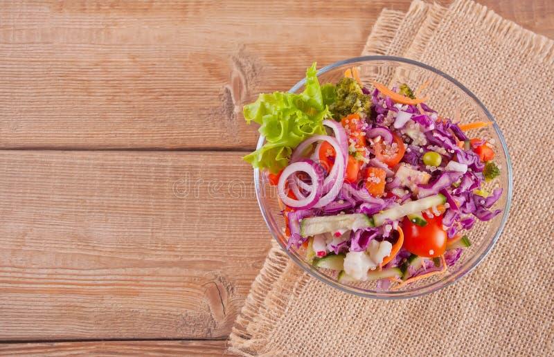 Ensalada fresca sana en cuenco con la col roja, el tomate, la quinoa, la ensalada verde y el r?bano en la tabla de madera Visi?n  fotografía de archivo