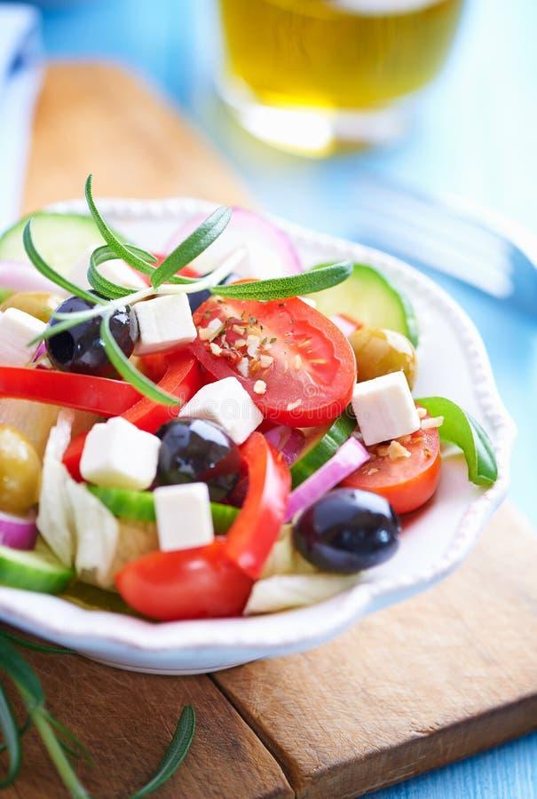 Ensalada griega con el queso feta, tomates de cereza, pimienta roja, aceitunas negras y verdes, pepino y romero fresco imagenes de archivo
