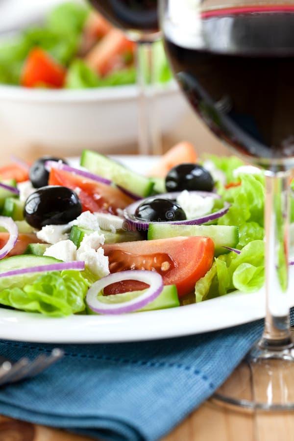 Ensalada griega con el vino imagen de archivo