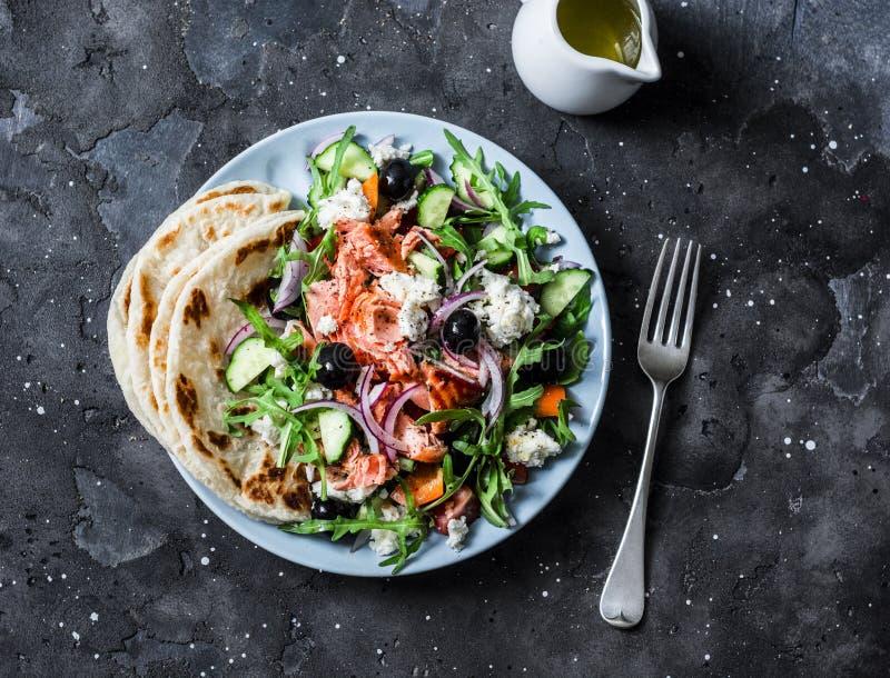 Ensalada griega con los salmones cocidos en un fondo oscuro, visi?n superior Comida mediterr?nea sana de la dieta foto de archivo