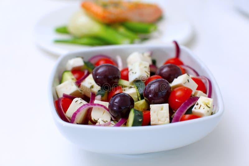 Ensalada griega con los tomates, el queso de queso Feta y las aceitunas imagen de archivo
