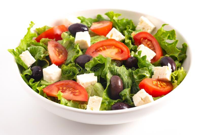 Ensalada griega con los tomates y el queso feta de las aceitunas aislados en un fondo blanco foto de archivo libre de regalías