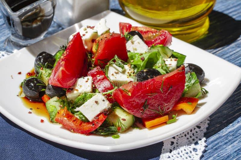 Ensalada griega de pepinos frescos, de tomates, de pimientas dulces, de la lechuga, del queso feta y de aceitunas con el aceite d imágenes de archivo libres de regalías