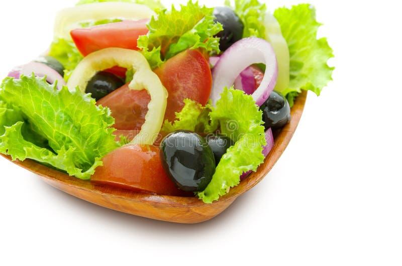 Ensalada griega de verduras brillantes frescas en una placa de madera aislada en el fondo blanco imagen de archivo