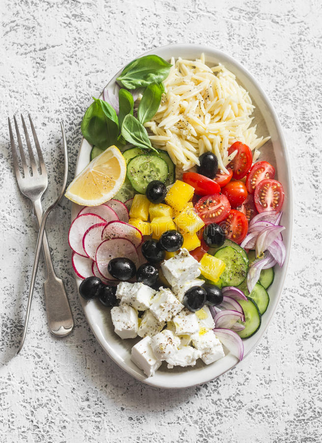 Ensalada griega del orzo del limón El queso Feta, orzo, tomates, pepinos, rábanos, aceitunas, sazona la ensalada con pimienta en  fotografía de archivo