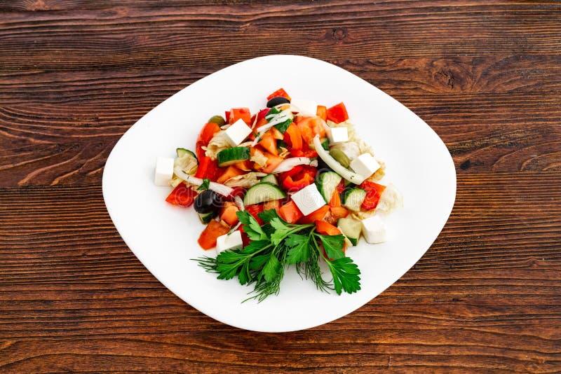 Ensalada griega del pepino fresco, del tomate, de la pimienta dulce, de la lechuga, de la cebolla roja, del queso feta y de las a foto de archivo