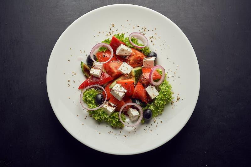 Ensalada griega del pepino fresco, del tomate, de la pimienta dulce, de la lechuga, de la cebolla roja, del queso feta y de las a fotografía de archivo
