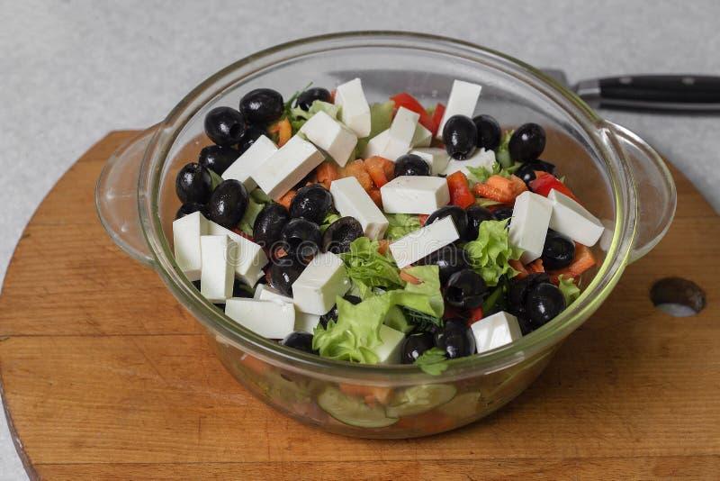Ensalada griega del pepino fresco, del tomate, de la pimienta dulce, de la lechuga, del queso feta y de las aceitunas con aceite  foto de archivo libre de regalías