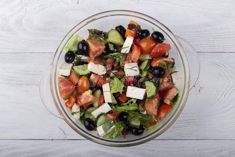 Ensalada griega del pepino fresco, del tomate, de la pimienta dulce, de la lechuga, del queso feta y de las aceitunas con aceite  fotos de archivo libres de regalías
