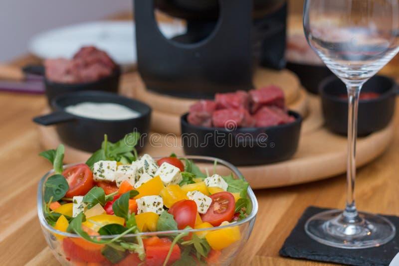 Ensalada griega delante de la 'fondue' de la carne fotografía de archivo
