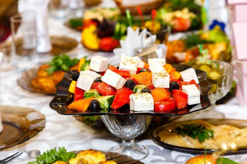 Ensalada griega en la tabla de banquete imagenes de archivo