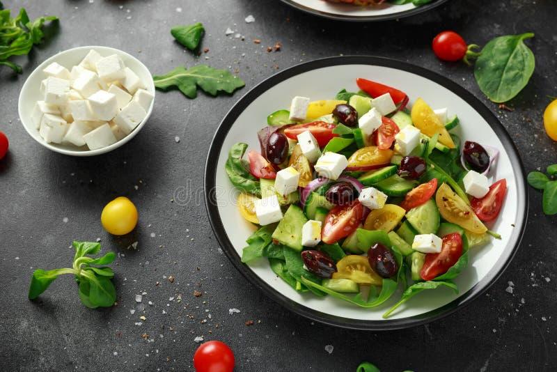 Ensalada griega fresca con el pepino, el tomate de cereza, la lechuga, la cebolla roja, el queso feta y las aceitunas negras Alim imagen de archivo