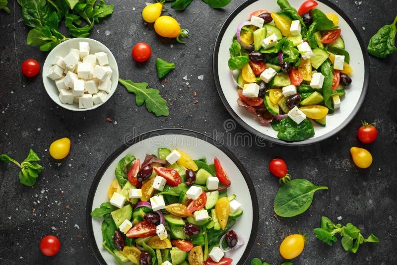 Ensalada griega fresca con el pepino, el tomate de cereza, la lechuga, la cebolla roja, el queso feta y las aceitunas negras Alim fotos de archivo