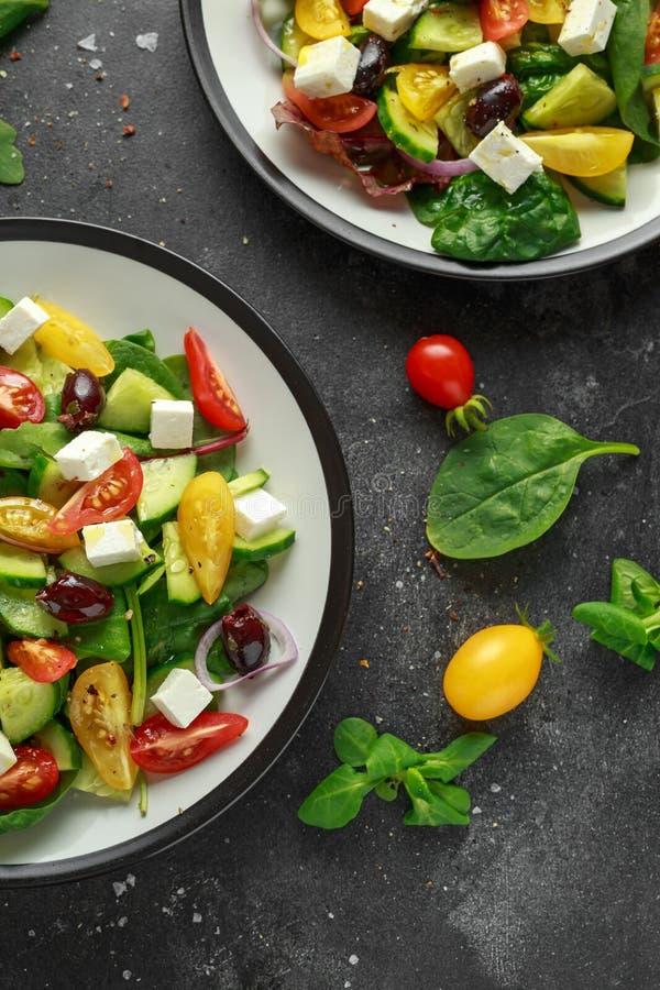 Ensalada griega fresca con el pepino, el tomate de cereza, la lechuga, la cebolla roja, el queso feta y las aceitunas negras Alim imagenes de archivo