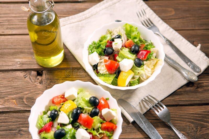 Ensalada griega fresca hecha del tomate de cereza, del queso Feta, de aceitunas, de la cebolla y de especias Ensalada César en un imagen de archivo libre de regalías
