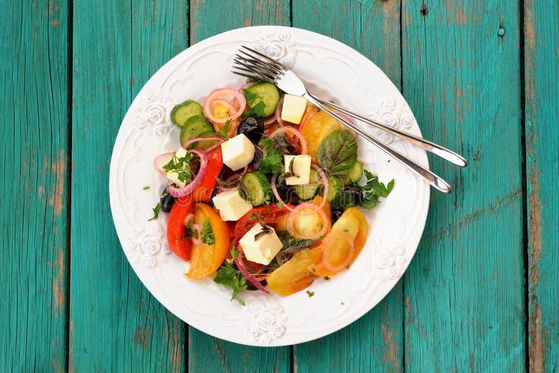 Ensalada griega hecha en casa del vegano con las verduras crudas y el queso feta i foto de archivo