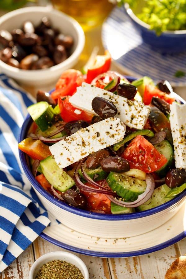 Ensalada griega Ensalada griega tradicional que consiste en verduras frescas tales como tomates, pepinos, pimientas, cebollas, or imágenes de archivo libres de regalías