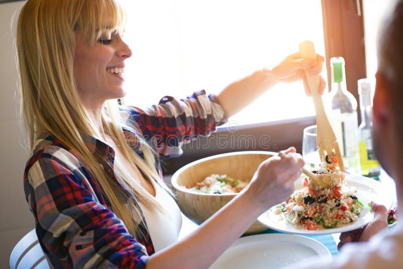 Ensalada hermosa de la quinoa de la porción de la mujer joven en su placa del novio en la cocina en casa imagen de archivo