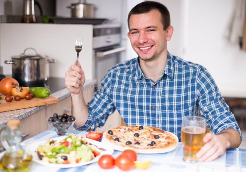 Ensalada masculina feliz de la pizza de la cena en la cocina imagenes de archivo