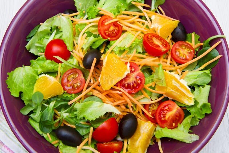Ensalada mezclada con los tomates en cuenco púrpura imágenes de archivo libres de regalías
