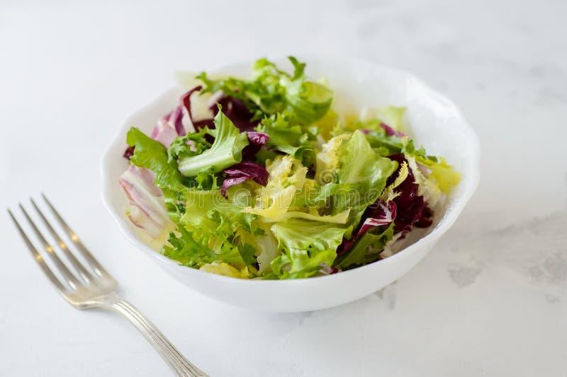 Ensalada mezclada de las verduras frescas (lechuga de iceberg, radicchio y frisee verdes) en el cuenco blanco foto de archivo libre de regalías