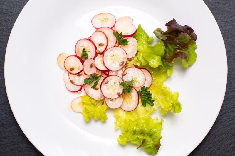 Ensalada orgánica del rábano de las rebanadas de la comida sana en la placa blanca en negro imagen de archivo libre de regalías