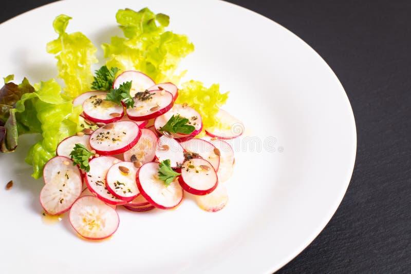 Ensalada orgánica del rábano de las rebanadas de la comida sana en la placa blanca en negro fotografía de archivo