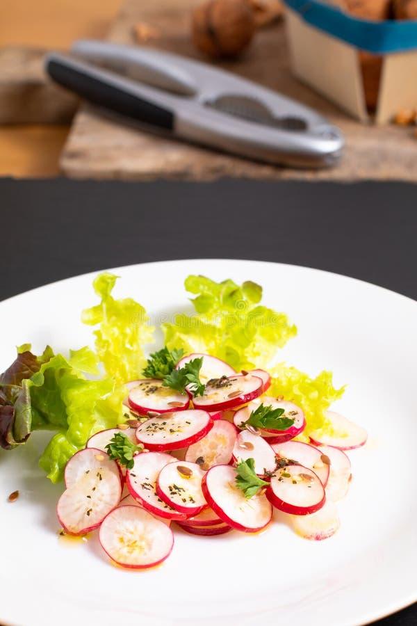 Ensalada orgánica del rábano de las rebanadas de la comida sana en la placa blanca en negro foto de archivo
