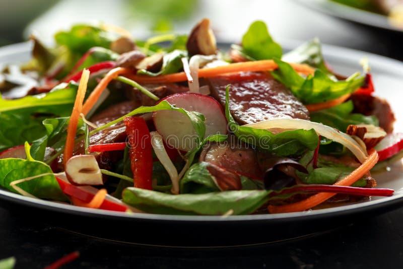 Ensalada picante de la carne de vaca con las zanahorias, el rábano, los brotes de haba, los chiles, las nueces y la mezcla verde imagen de archivo libre de regalías