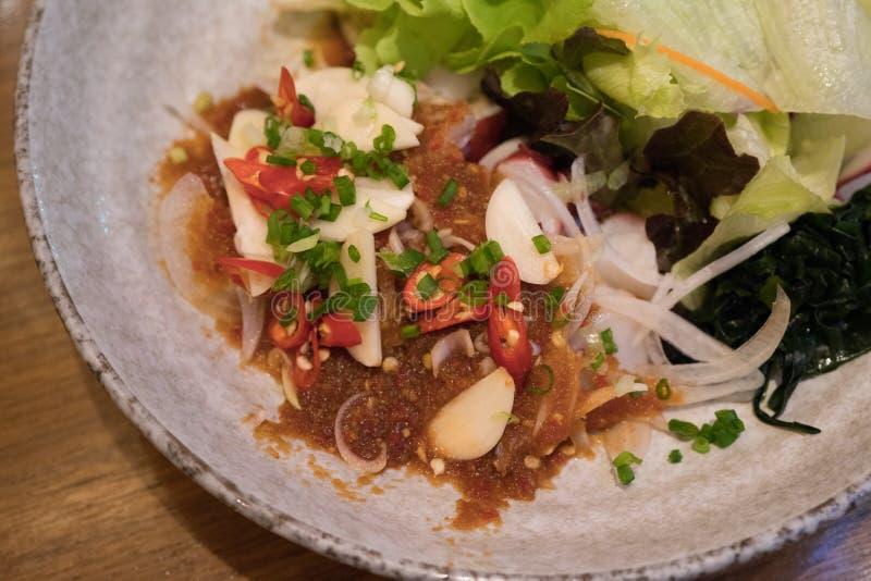 Ensalada picante del shashimi de Tako con lechuga, la cebolla, y la alga marina frescas imágenes de archivo libres de regalías