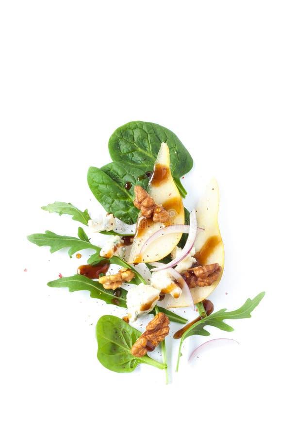 Ensalada - queso verde, pera, arugula, nueces, cebolla roja y vestido imagen de archivo libre de regalías