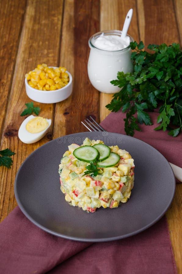 Ensalada rusa tradicional con los palillos del cangrejo, los pepinos frescos, el maíz y los huevos hervidos fotos de archivo libres de regalías