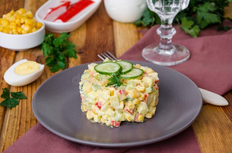 Ensalada rusa tradicional con los palillos del cangrejo, los pepinos frescos, el maíz y los huevos hervidos foto de archivo