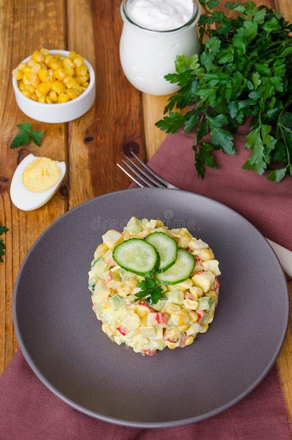 Ensalada rusa tradicional con los palillos del cangrejo, los pepinos frescos, el maíz y los huevos hervidos foto de archivo libre de regalías
