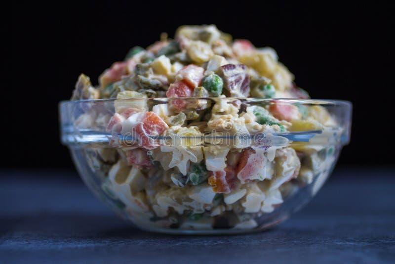 Ensalada russa ou salada Olivier no fundo escuro da bacia de vidro fotos de stock