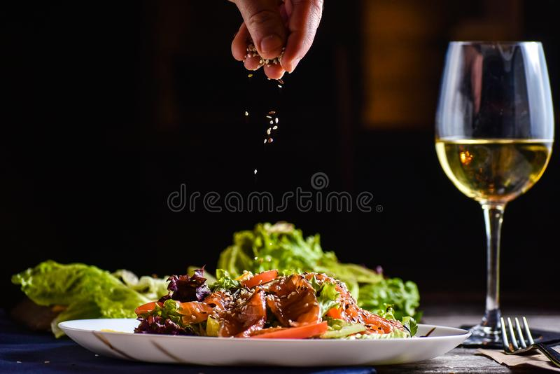 Ensalada sabrosa y fresca con los salmones fritos, verdes, tomate, aceite de oliva, sésamo, queso de la nata foto de archivo libre de regalías