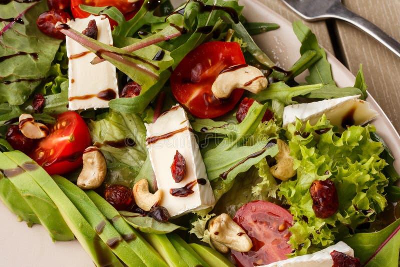 Ensalada sabrosa y sana con arugula, el brie, el queso, el aguacate, los tomates de cereza, el arándano seco y los anacardos Visi foto de archivo