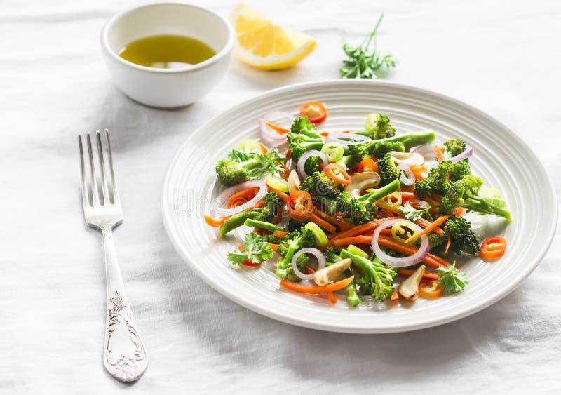 Ensalada sana con bróculi y zanahorias en una placa blanca imagenes de archivo
