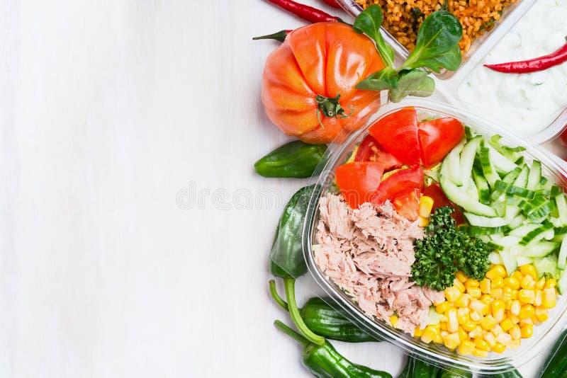 Ensalada sana con el atún, el maíz, el pepino y los tomates en fiambrera en el fondo de madera blanco, visión superior, espacio d fotografía de archivo